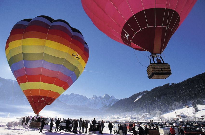 Two colorful hot air balloons over the mountains in winter