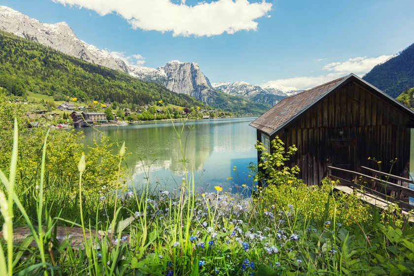 Flower field in front of a lake with clear water and a wooden cottage. Spectacular rock formations in the bachground