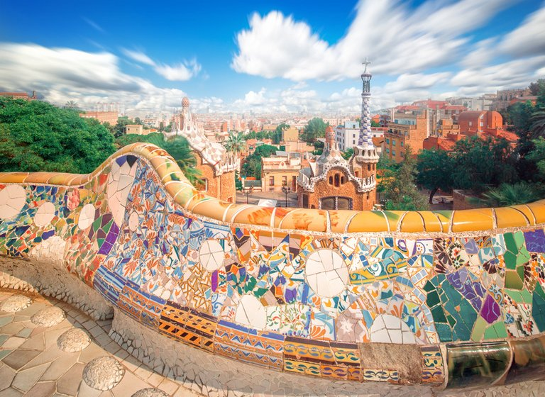 Colorful tiles in Parc Güell in Barcelona with a view on the surrounding buildings