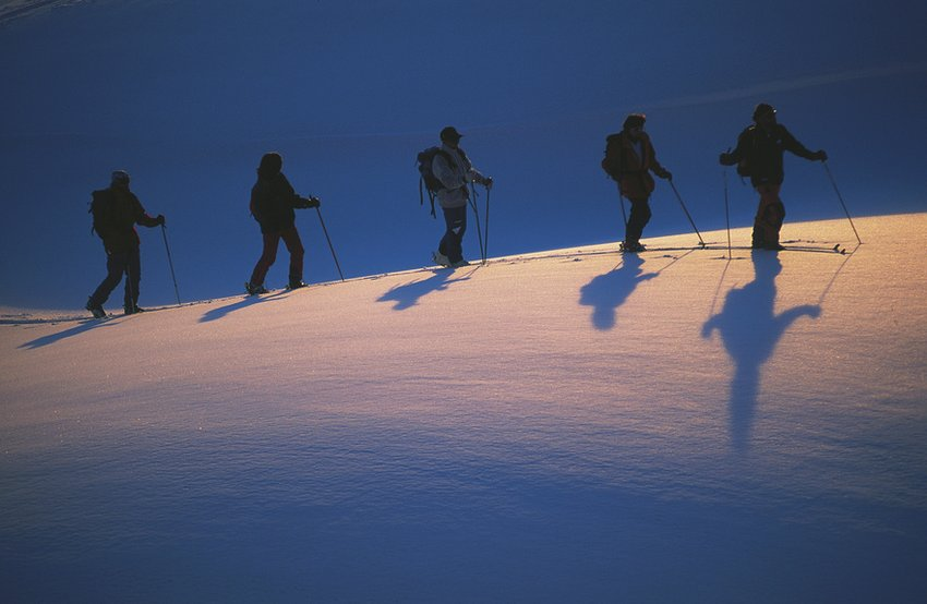 Tracking tours in the snow. A group of hikers are walking through the deep snow in Steiermark, Austria, underneath the a cloudless sky