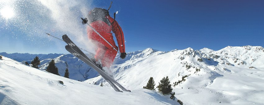 Extreme skiing in snow-covered mountain landscape. Skier making a junp