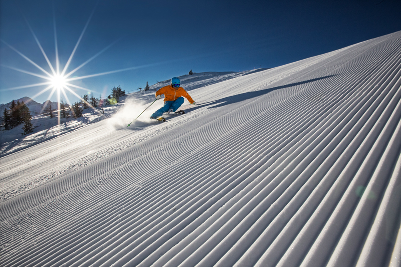 Man skiing on the freshly prepared slope, blue skies and sunshine