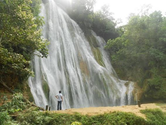 Man in front of a waterfall in the dominican republic in the jungle