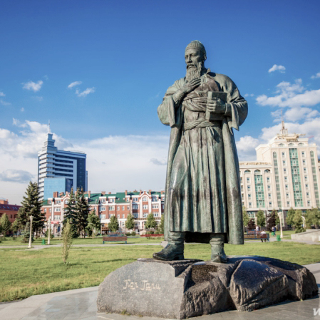 Statue in a park with historic buildings in the back, Russia
