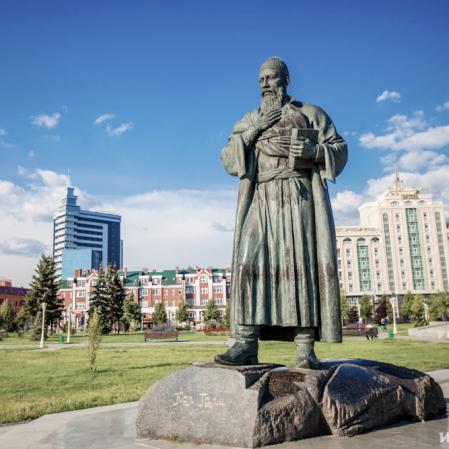 Statue in Park mit historischen Häusern im Hintergrund, Russland